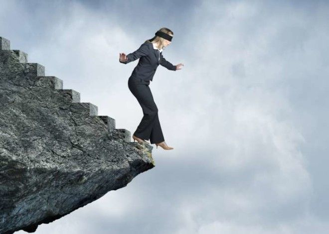 Blindfolded Businesswoman About To Step Off Cliff Stairs