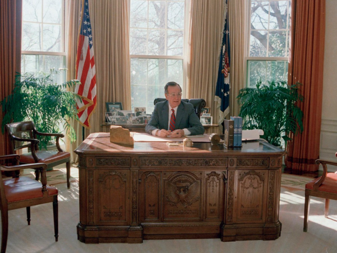 George H.W. Bush's workspace looked a bit neater, as he kept his personal photos on a table behind his desk in 1989.
