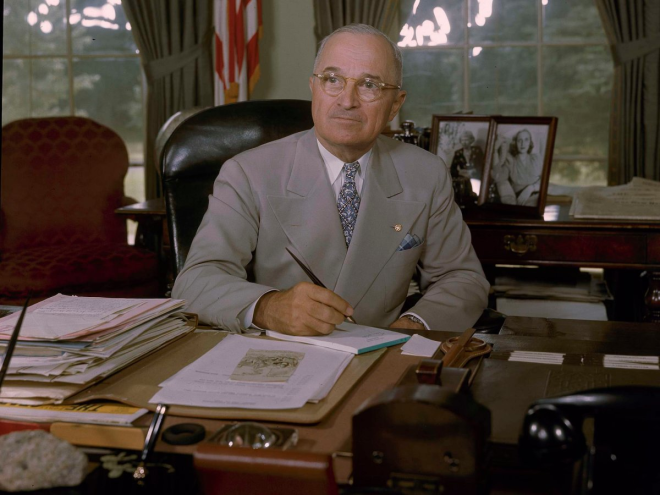 Harry S. Truman's desk also featured the familiar heaps of paper, with a table of mementos and family photos in the background.