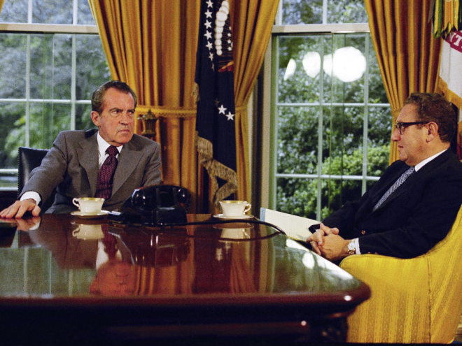 In this 1973 photo, Richard Nixon talks with Henry Kissinger over tea or coffee at his desk. On the table behind him is a bust of Abraham Lincoln, along with family photos.