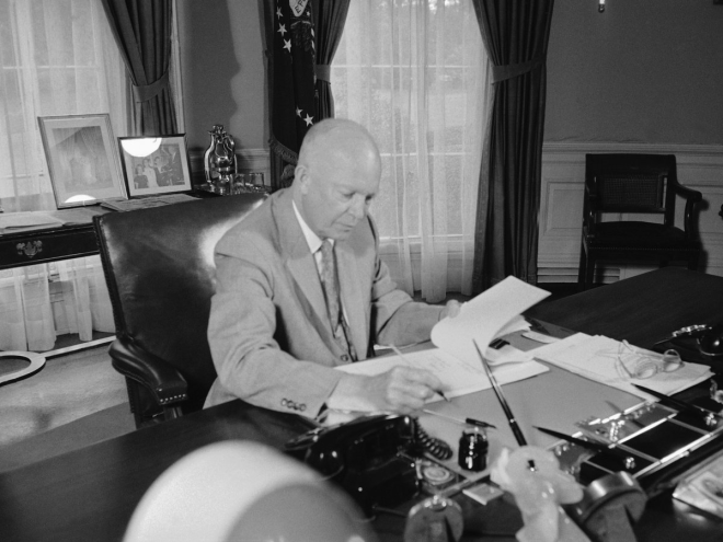 In this similar shot, Kennedy's predecessor, Dwight D. Eisenhower, works on a desk featuring a phone, ink, and lots of documents.