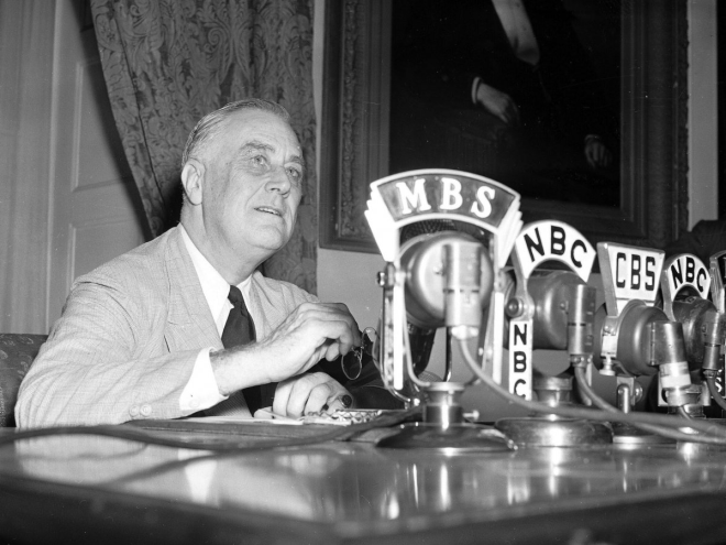 Microphones from various news outlets lined Franklin D. Roosevelt's desk as he prepared to make an announcement.