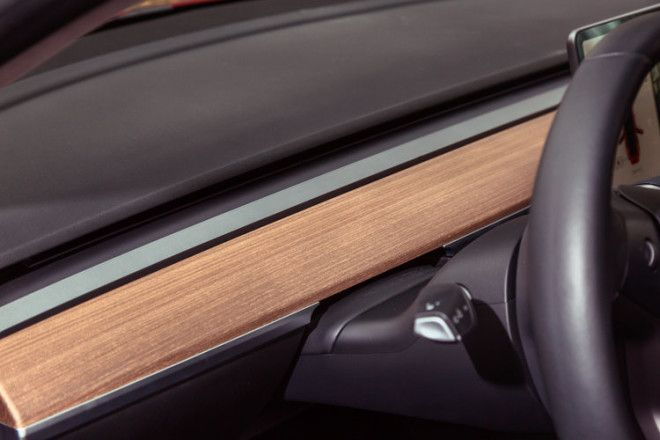 The open-grain wood and brushed metallic trim is the only real deviation from the black interior color.