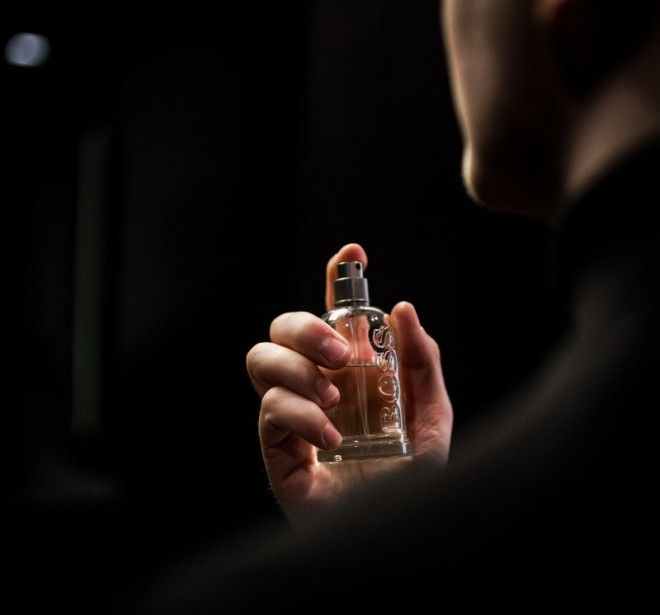 A man putting on a perfume.
