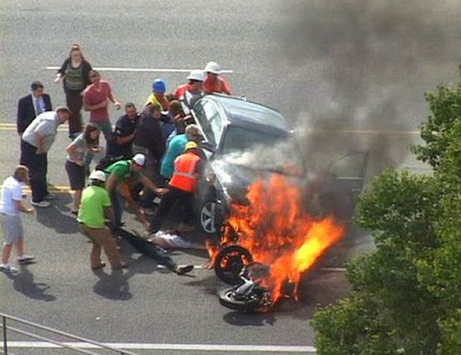 When a trapped motorcyclist was helped by bystanders who literally lifted the car off him.