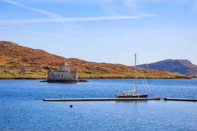 Kisimul Castle on the island of Barra one of the outer hebrides islands and a sailing boat moored on the new marina poonton