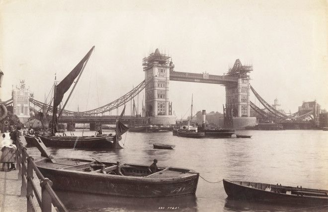 The Tower Bridge is seen under construction with river traffic in the foreground.